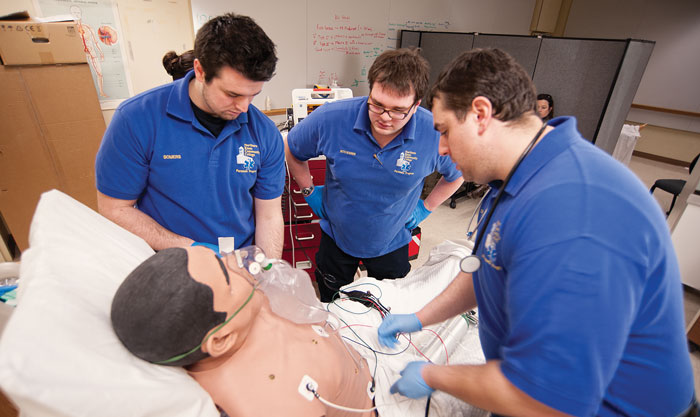 Students in NECC's paramedic program ponder over what ails Stan, an eerily lifelike mannequin. Photos by Kevin Harkins.