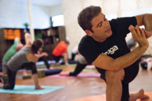 Yoga instructor Chuck Raffoni demonstrates a stretch during his Broga class at Windsor Studio. Photo by Adrien Bisson.
