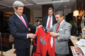 Ted Lenosis presents the jersey of the NHL's Washington Capitals to U.S. Secretary of State John Kerry. Leonsis also owns the teams' home, the Verizon Center, which revitalized a deteriorating section of the nation's capital. Photo courtesy Monumental Sports Entertainment.