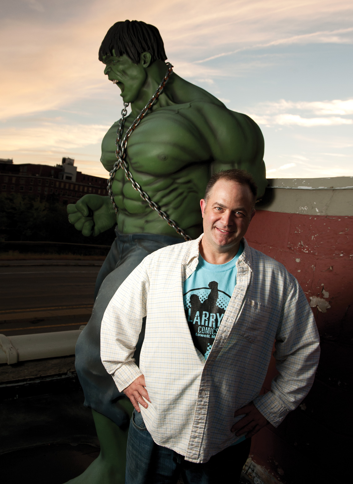 Larry Doherty poses with a life-size Incredible Hulk on the roof of his store, a visible sign to drivers along the VFW highway in Lowell. Photo by Kevin Harkins.